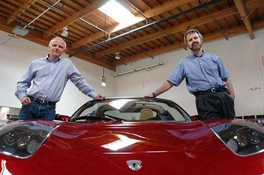 Dois homens junto de um carro.